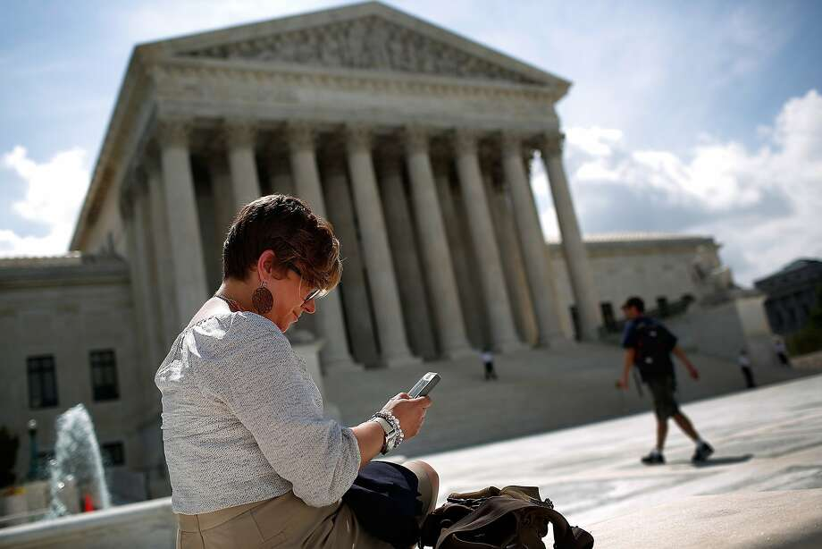 Kirsten Luna of Michigan looks at her phone outside the U.S. Supreme Court after the justices' unanimous decision. Photo: Win McNamee, Getty Images