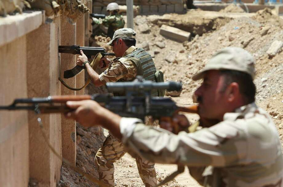 Kurdish peshmerga fighters take their positions behind a wall on the closest front line with militants from the al-Qaida-inspired Islamic State in Iraq and the Levant (ISIL), in Tuz Khormato, 100 kilometers (62 miles) south of the oil rich province of Kirkuk, northern Iraq, Wednesday, June 25, 2014.  Photo: Hussein Malla, STF / AP