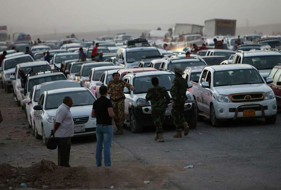 Fleeing Iraqi citizens from Mosul and other northern towns, wait in a long traffic queue at a Kurdish security forces checkpoint, at a highway between the Iraqi city of Mosul and the Kurdish city of Irbil, in the Khazer area northern Iraq, Wednesday June 25, 2014.  Photo: Hussein Malla, Associated Press / AP