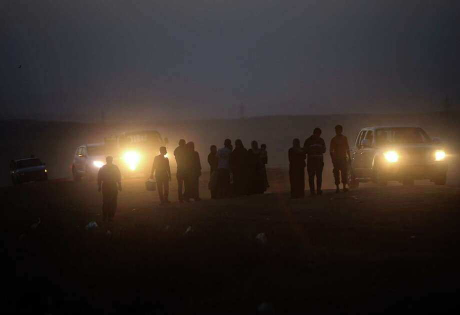 Fleeing Iraqi citizens from Mosul and other northern towns are seen silhouetted as they walk on a desert field to cross to secure areas, in the Khazer area between the Iraqi city of Mosul and the Kurdish city of Irbil, northern Iraq, Wednesday June 25, 2014. Photo: Hussein Malla, Associated Press / AP