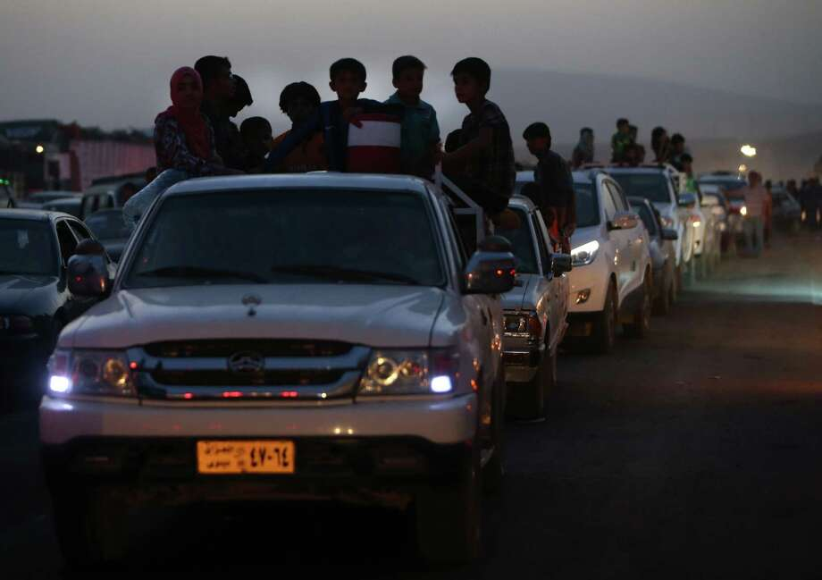 Fleeing Iraqi citizens from Mosul and other northern towns are seen on their pickups and cars waiting in a queue to cross to secure areas at a Kurdish security forces checkpoint, in the Khazer area between the Iraqi city of Mosul and the Kurdish city of Irbil, northern Iraq, Wednesday June 25, 2014.  Photo: Hussein Malla, Associated Press / AP