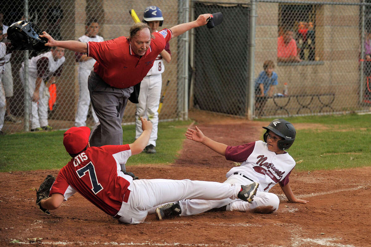 Stamford Nationals' Armando Gonzalez is called safe at home despite the efforts of Stamford Americans' Nick Otis during their baseball game at Scalzi Park in Stamford, Conn., on Wednesday, June 25, 2014. The Stamford National team won 14-2 in four innings.