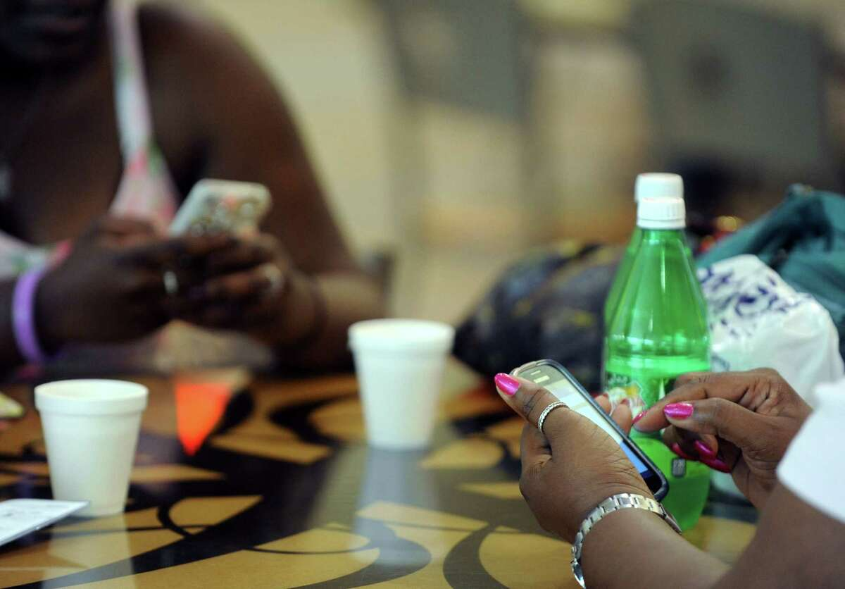 Shoppers check their phones while having lunch at Colonie Center on Wednesday June 25, 2014, in Colonie, N.Y. The Supreme Court ruling Wednesday on phone privacy ruled that police cannot search the digital contents of cellphones without a warrant. (Michael P. Farrell/Times Union)