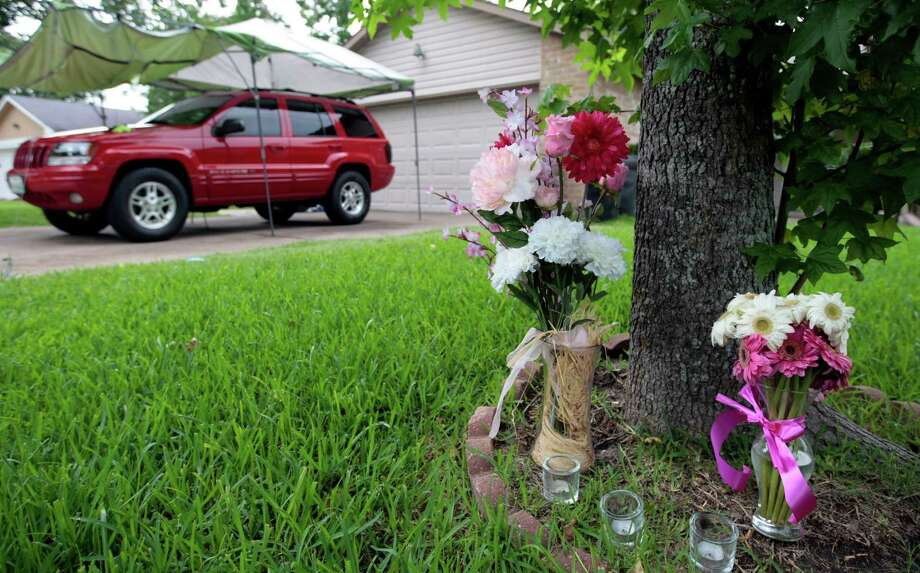Vases of flowers outside a Fort Bend County home Wednesday offer the only sign that three members of a Stafford family had died of gunshot wounds inside. Photo: Billy Smith II, Staff / © 2014 Houston Chronicle