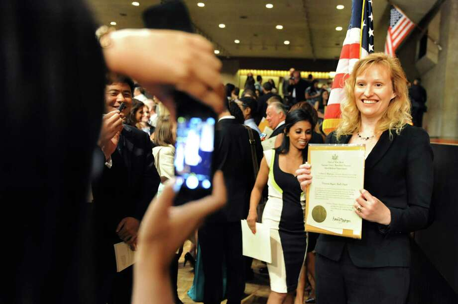 Newly minted lawyer Victoria Hall-Sturt of England, right, gets her picture taken following her admissions ceremony to the New York State Bar  Wednesday, June 25, 2014, at the Empire State Plaza Convention Center in Albany, N.Y. Over 500 attorneys were sworn in as members of the New York State Bar. (Cindy Schultz / Times Union) Photo: Cindy Schultz / 00027439A