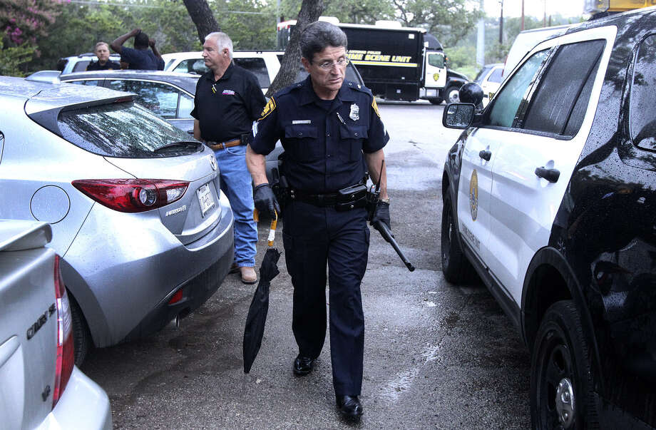 Police Officer R.R. Sanchez carries a rifle as he walks to a patrol car outside the Avistar at Chase Hill apartment complex. Photo: Photos By John Davenport / San Antonio Express-News / ©San Antonio Express-News/John Davenport
