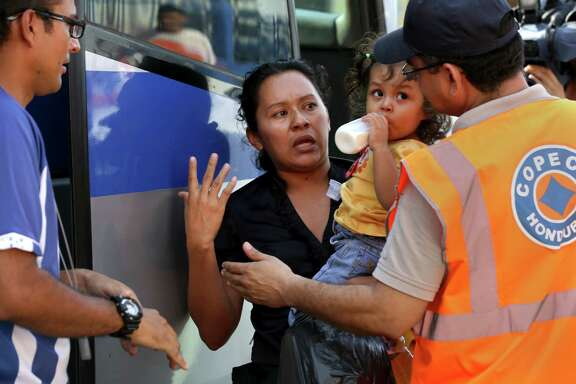 Honduras Disaster Agency workers try to calm Antonia Marquez, holding her daughter, after she arrived by bus with other adults and children who were deported from Mexico on Wednesday.