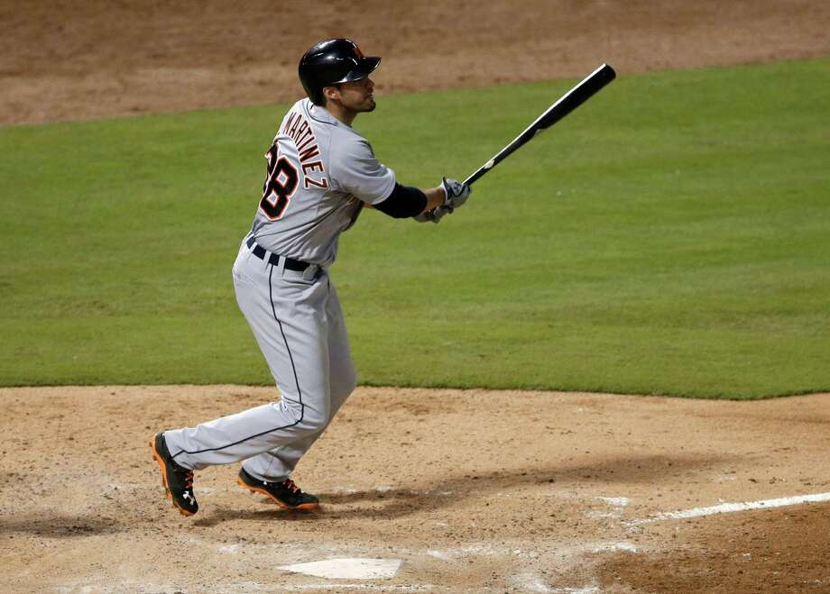 Detroit Tigers' J.D. Martinez follows throgh on a solo home run swing off a pitch from Texas Rangers relief pitcher Shawn Tolleson in the fifth inning of a baseball game, Wednesday, June 25, 2014, in Arlington, Texas. (AP Photo/Tony Gutierrez) Photo: Tony Gutierrez, Associated Press / AP