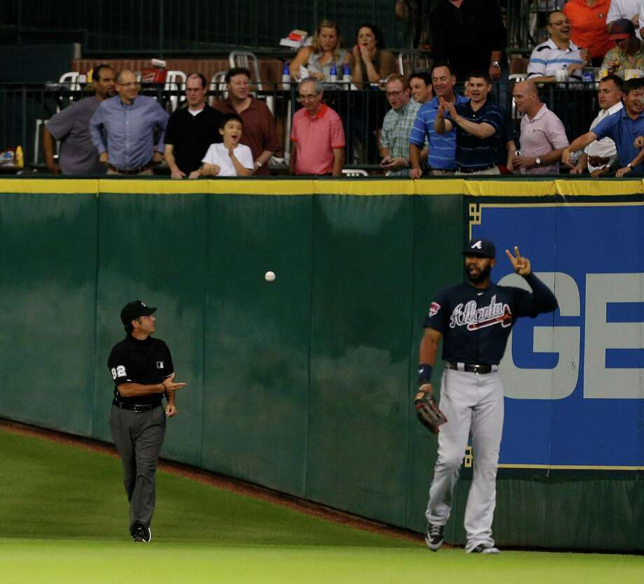 Umpire James Hoye tosses the ball to the fans after ruling that a ball hit by Jon Singleton in the fourth inning that became lodged under the padding on the outfield wall was a ground-rule double. Photo: Karen Warren, Staff / © 2014 Houston Chronicle
