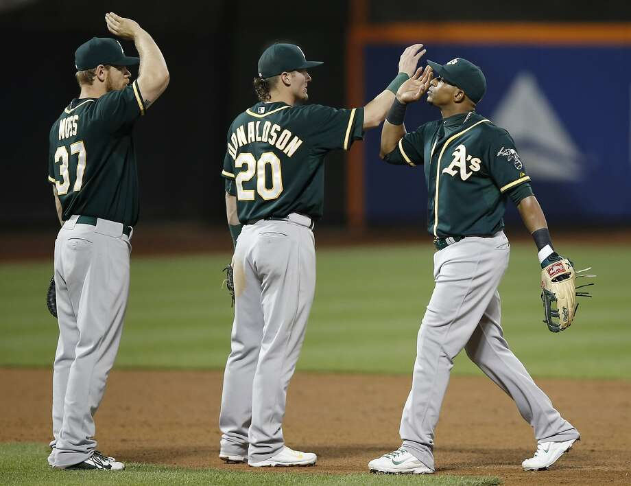 Brandon Moss and Josh Donaldson salute Yoenis Céspedes, who earlier hit a three-run double. Photo: Kathy Willens, Associated Press