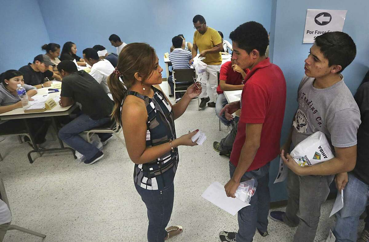 Dunia Menjivair, a volunteer worker at the Center of Attention for Returned Migrants, hands out cards to the returnees.