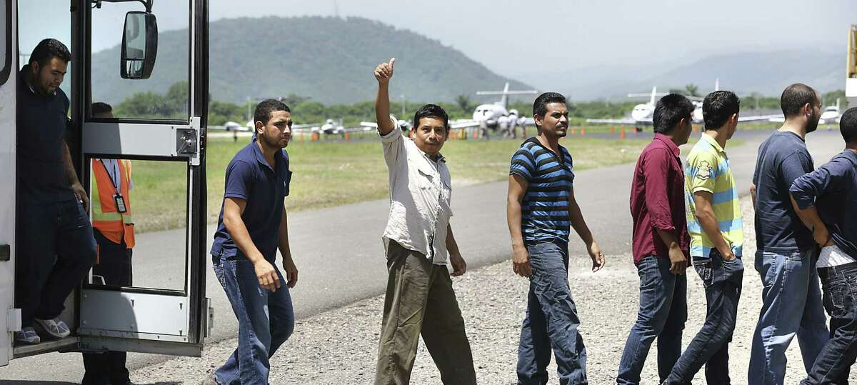 Honduran migrants who arrived by plane at the San Pedro Sula airport get off a bus and head for processing by volunteer workers.