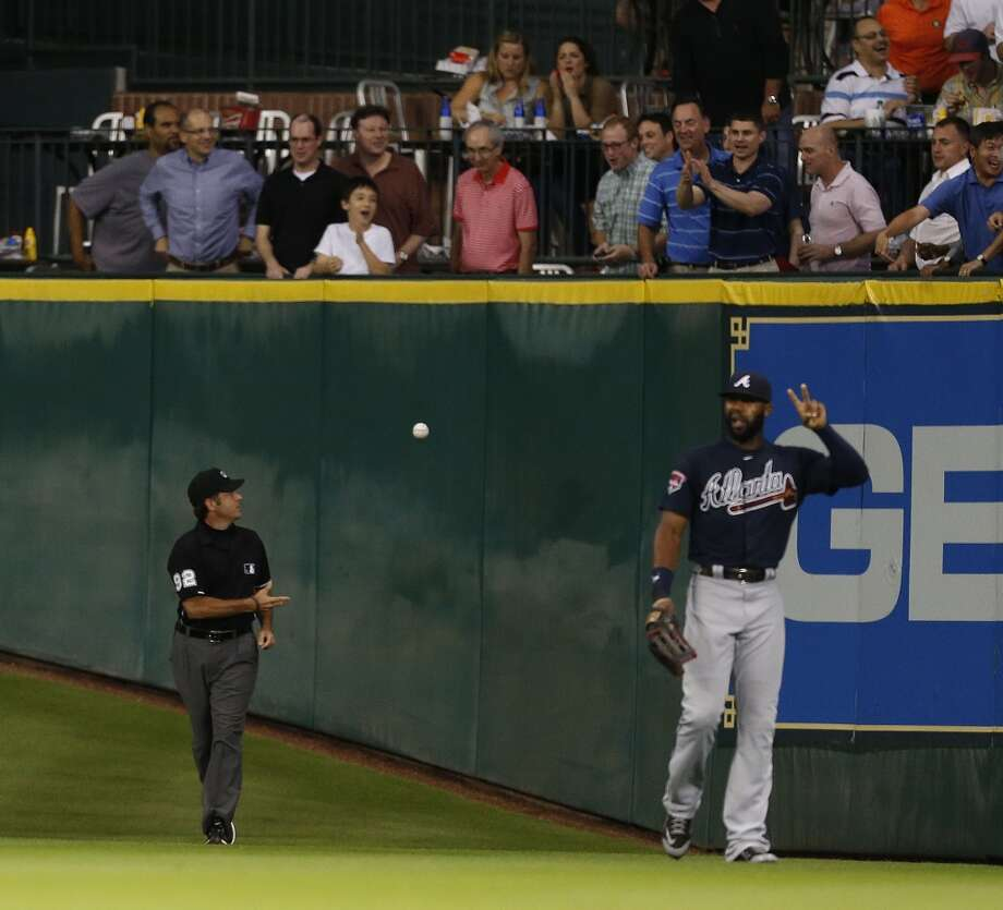 Umpire James Hoye (92) tosses the ball to the outfield fans after ruling on a ground-rule double during the fourth inning. Photo: Karen Warren, Houston Chronicle