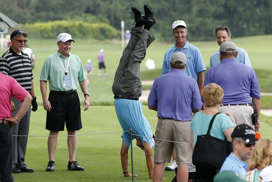 Senior golfer Esteban Toledo, center, of Mexico, does a hand stand on the first tee before teeing off in the Pro-Am round of the Senior Players Championship golf tournament at Fox Chapel Golf Club in Pittsburgh, Wednesday, June 25, 2014. Tournament play starts Thursday. (AP Photo/Gene J. Puskar) Photo: Gene J. Puskar, Associated Press