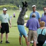 Senior golfer Esteban Toledo, center, of Mexico, does a hand stand on the first tee before teeing off in the Pro-Am round of the Senior Players Championship golf tournament at Fox Chapel Golf Club in Pittsburgh, Wednesday, June 25, 2014. Tournament play starts Thursday. (AP Photo/Gene J. Puskar)