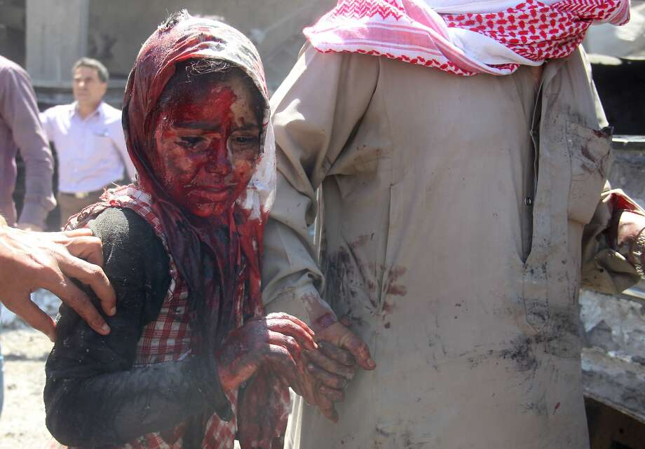TOPSHOTS GRAPHIC CONTENT A Syrian girl with her face covered in blood walks away from the site of a reported barrel-bomb attack by Syrian government forces in the northern city of Aleppo on June 25, 2014. Syria's war has killed more than 162,000 people and forced nearly half the population to flee their homes. AFP PHOTO /AMC / KHALED KHATIBKHALED KHATIB/AFP/Getty Images Photo: Khaled Khatib, AFP/Getty Images