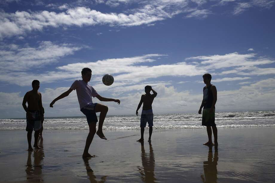 Residents and tourists play soccer on Ponta Negra beach in Natal, Brazil, Wednesday, June 25, 2014. Natal is one of many cities hosting the World Cup soccer tournament this month. (AP Photo/Hassan Ammar) Photo: Hassan Ammar, Associated Press