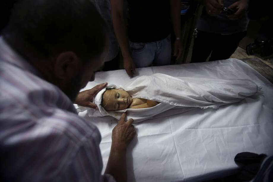 A Palestinian medic cleans the body of a three-year-old girl during her funeral at a morgue in Gaza City, in the northern Gaza Strip, Wednesday, June 25, 2014. A rocket fired by Palestinian militants toward Israel exploded in the northern Gaza Strip early Wednesday, killing a 3-year-old girl and wounding three other people, a medical official said. Ashraf al-Kidra said it was not clear whether the rocket was misfired, or whether an Israeli rocket-defense system intercepted it and caused it to explode over Palestinian territory. (AP Photo/Adel Hana) Photo: Adel Hana, Associated Press