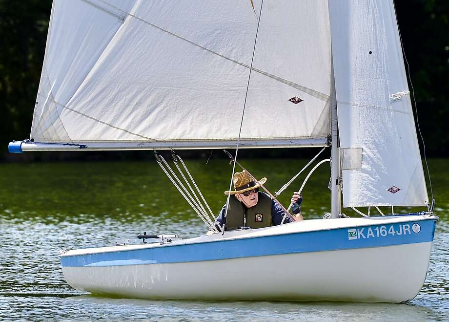 "Jim Randolph, of Mission, hopes to catch some wind while sailing his 16-foot boat named ""Sweet Sue,"" on Wednesday, June 25, in the lake at Shawnee Mission Park in Shawnee, Kan.  (AP Photo/The Kansas City Star, Allison Long) Photo: Allison Long, Associated Press"