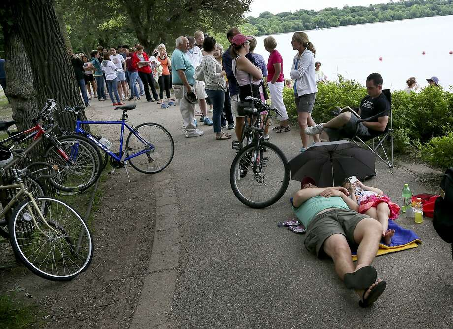Sam Runge and daughter Zoe, 6, of Richfield rest while waiting in line at the Lake Harriet Bandshell, in Minneapolis, Wednesday, June 25, 2014, for general public tickets for a visit Thursday by President Obama at the Lake Harriet Bandshell. Officials have said previously that they picked Minnesota because of a recent law change that will boost a long-stagnant minimum wage. Under the law, the wage will climb to $9.50 per hour by 2016 through a series of incremental increases. (AP Photo/The Star Tribune, David Joles) Photo: David Joles, Associated Press
