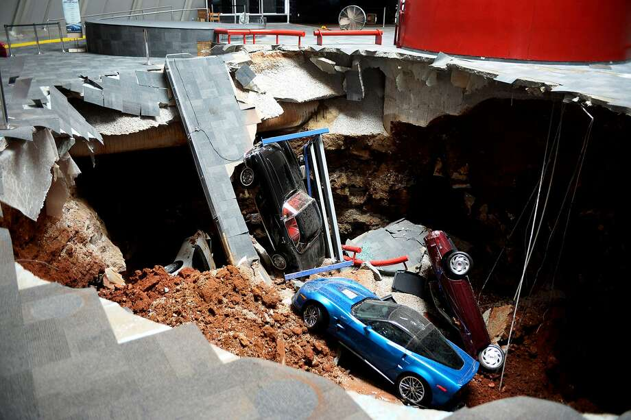 In this Wednesday, Feb. 12, 2014 photo, cars lie in a sinkhole that opened up at the Skydome showroom in the National Corvette Museum in Bowling Green, Ky. The sinkhole that swallowed eight cars at the has become such an attraction that officials want to preserve it. They may even put one or two of the cars back inside the hole. The board of the museum in Kentucky voted Wednesday, June 25, 2014 to preserve a large section of the sinkhole that opened beneath the museum in February. (AP Photo/Michael Noble Jr.) Photo: Michael Noble Jr., Associated Press