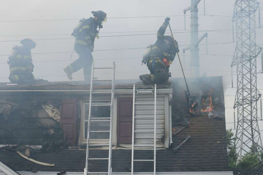 Firefighters work on the roof of a burning home on Highview Drive in Clifton, N.J. on Wednesday, June 25, 2014. The 2-alarm fire caused heavy damage and Deputy Fire Chief Michael J. Sauer said a firefighter was taken to the hospital with possible heat exhaustion. (AP Photo/The Record, Northjersey.com, Tariq Zehawi) Photo: Tariq Zehawi, Associated Press