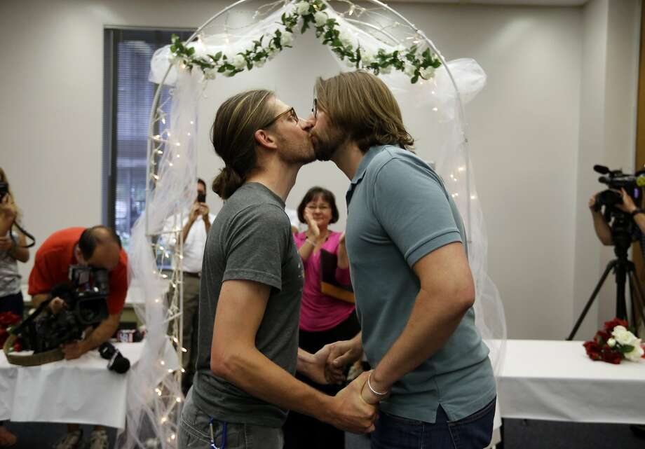 Jake Miller, 30, and Craig Bowen, 35, right, kiss after being married by Marion County Clerk Beth White, center, in Indianapolis, Wednesday, June 25, 2014. A federal judge struck down Indiana's ban on same-sex marriage Wednesday in a ruling that immediately allowed gay couples to wed. (AP Photo/Michael Conroy) Photo: Michael Conroy, Associated Press