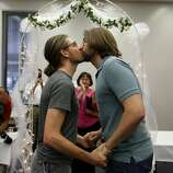 Jake Miller, 30, and Craig Bowen, 35, right, kiss after being married by Marion County Clerk Beth White, center, in Indianapolis, Wednesday, June 25, 2014. A federal judge struck down Indiana's ban on same-sex marriage Wednesday in a ruling that immediately allowed gay couples to wed. (AP Photo/Michael Conroy)