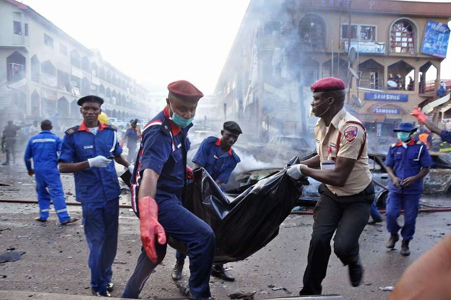 Rescue workers carry the remains of a person in a body bag, after a explosion at a shopping mall in Abuja, Nigeria, Wednesday, June 25, 2014. An explosion rocked a shopping mall in Nigeria's capital, Abuja, on Wednesday and police say at least over 20 people have been killed and many wounded. Witnesses say body parts were scattered around the exit to Emab Plaza, in the upscale Wuse 11 suburb. (AP Photo/Olamikan Gbemiga) Photo: Olamikan Gbemiga, Associated Press