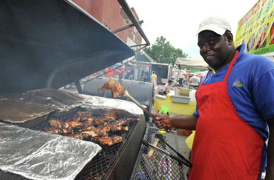 Dale Brown of New Paltz barbecues chicken at the Jamaica Choice booth during the Troy Pig Out on Saturday July 13, 2013 in Troy, N.Y.  (Michael P. Farrell/Times Union) ORG XMIT: MER2013071316115420 Photo: Michael P. Farrell / 00023055B
