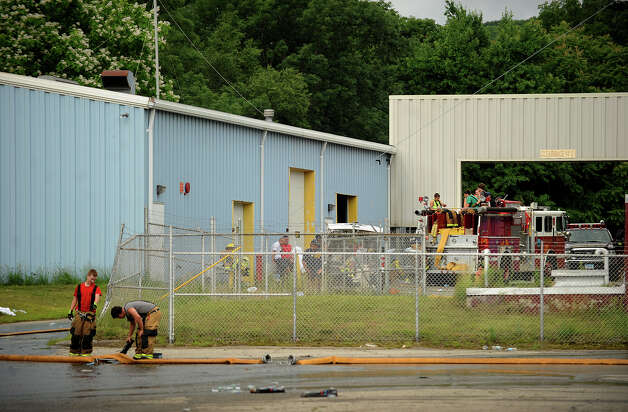 Firefighters are on scene in the aftermath of an early morning fire at the Latex International factory at 510 River Road in Shelton, Conn. on Thursday, June 26, 2014. Photo: Brian A. Pounds / Connecticut Post