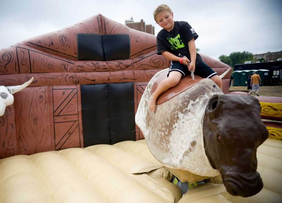 Mark Kuhar, 5, rides the mechanical bull during Pork in the Park at Mill River Park on Saturday, July 13, 2013. Photo: Lindsay Perry