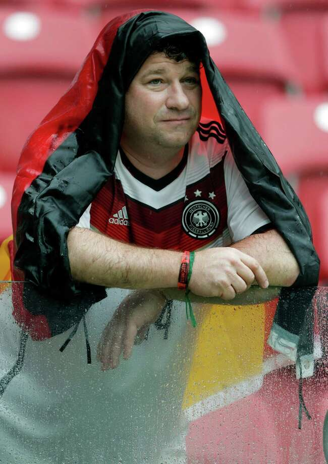A fan is covered with a German flag as he waits for the beginning of the group G World Cup soccer match between the USA and Germany at the Arena Pernambuco in Recife, Brazil, Thursday, June 26, 2014. (AP Photo/Matthias Schrader) Photo: Matthias Schrader, Associated Press / AP