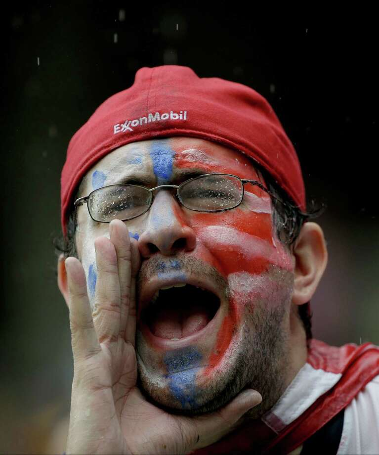 A rain soaked supporter cheers for the USA national team before the group G World Cup soccer match between the United States and Germany at the Arena Pernambuco in Recife, Brazil, Thursday, June 26, 2014. (AP Photo/Julio Cortez) Photo: Julio Cortez, Associated Press / AP