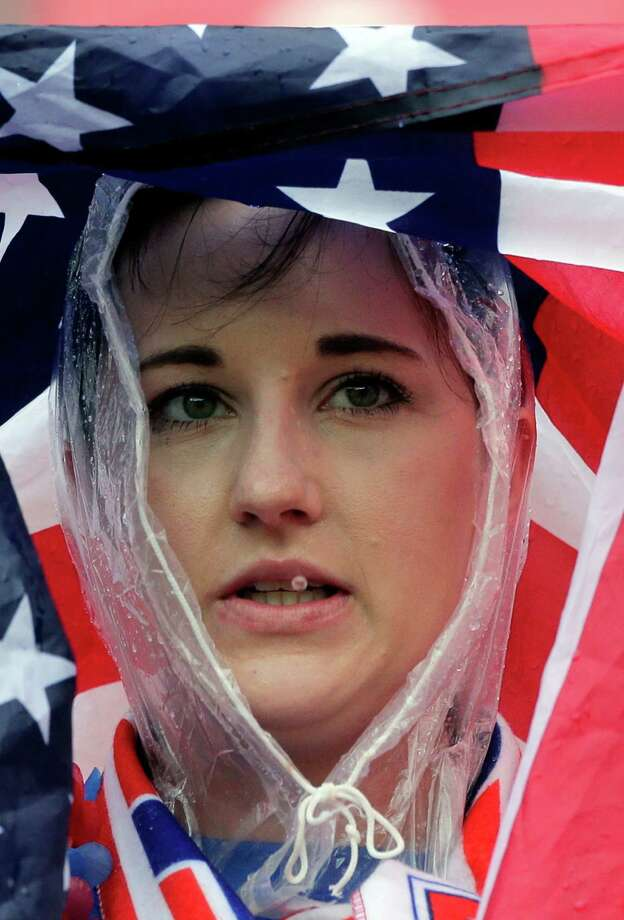 A US supporter uses a American flag to protect herself against the rain during the group G World Cup soccer match between the USA and Germany at the Arena Pernambuco in Recife, Brazil, Thursday, June 26, 2014. (AP Photo/Matthias Schrader) Photo: Matthias Schrader, Associated Press / AP