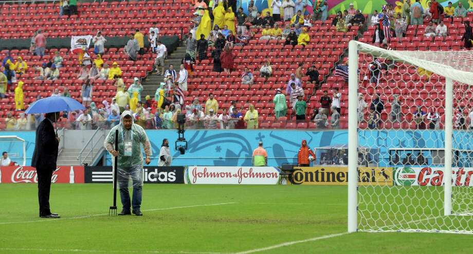 A FIFA official and grounds worker inspect the pitch after heavy rain before the group G World Cup soccer match between the United States and Germany at the Arena Pernambuco in Recife, Brazil, Thursday, June 26, 2014. (AP Photo/Julio Cortez) Photo: Julio Cortez, Associated Press / AP