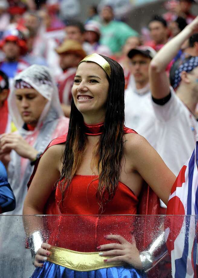 "A USA supporter, dressed as ""Wonder Woman"" waits in the rain for the group G World Cup soccer match between the United States and Germany at the Arena Pernambuco in Recife, Brazil, Thursday, June 26, 2014. (AP Photo/Julio Cortez) Photo: Julio Cortez, Associated Press / AP"