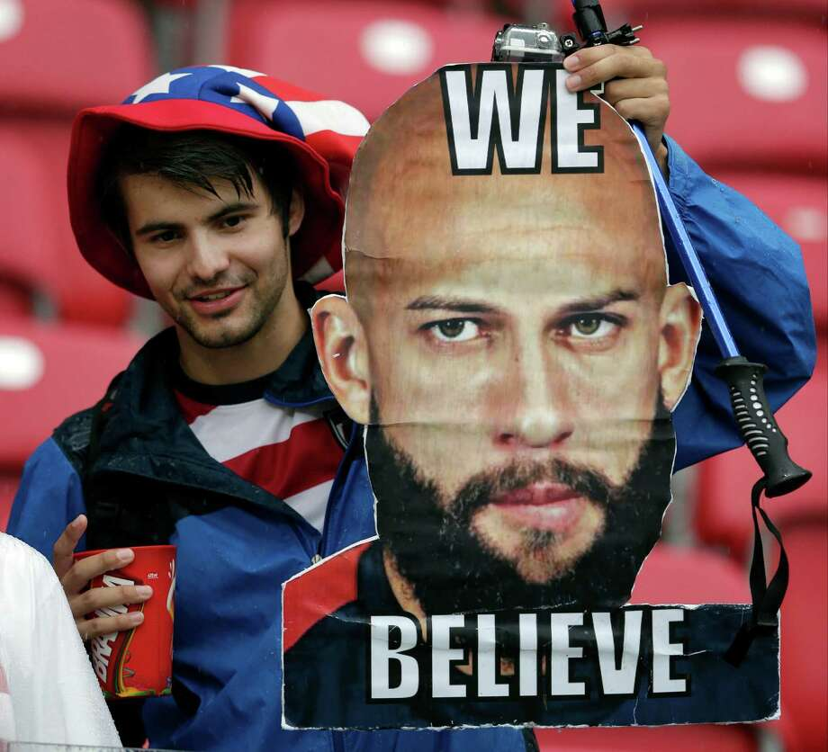 A fan holds a photo of United States' goalkeeper Tim Howard prior to the group G World Cup soccer match between the USA and Germany at the Arena Pernambuco in Recife, Brazil, Thursday, June 26, 2014. (AP Photo/Matthias Schrader) Photo: Matthias Schrader, Associated Press / AP