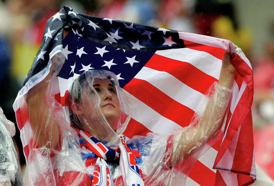 A US supporter uses an American flag to protect herself against the rain during the group G World Cup soccer match between the USA and Germany at the Arena Pernambuco in Recife, Brazil, Thursday, June 26, 2014. (AP Photo/Matthias Schrader) Photo: Matthias Schrader, Associated Press / AP