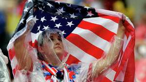 A US supporter uses an American flag to protect herself against the rain during the group G World Cup soccer match between the USA and Germany at the Arena Pernambuco in Recife, Brazil, Thursday, June 26, 2014. (AP Photo/Matthias Schrader)