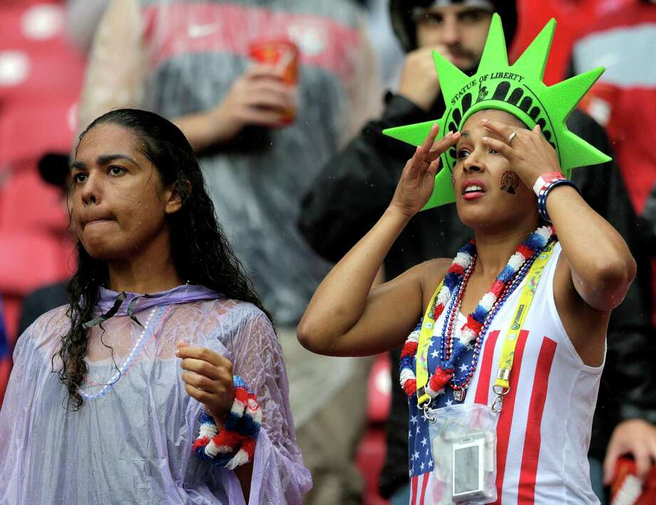Rain soaked fans wait for the start of the group G World Cup soccer match between the United States and Germany at the Arena Pernambuco in Recife, Brazil, Thursday, June 26, 2014. (AP Photo/Julio Cortez) Photo: Julio Cortez, Associated Press / AP