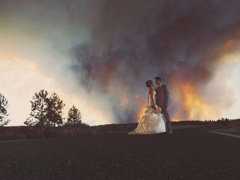 Newlyweds Michael Wolber and April Hartley had their wedding cut short on Saturday by the threat of fire, but they paused for pictures as the wildfire burned in the background. Because of the approaching fire, the minister conducted an abbreviated ceremony and the wedding party was evacuated to a Bend, Oregon, park. Photo: Josh Newton, HONS / Josh Newton