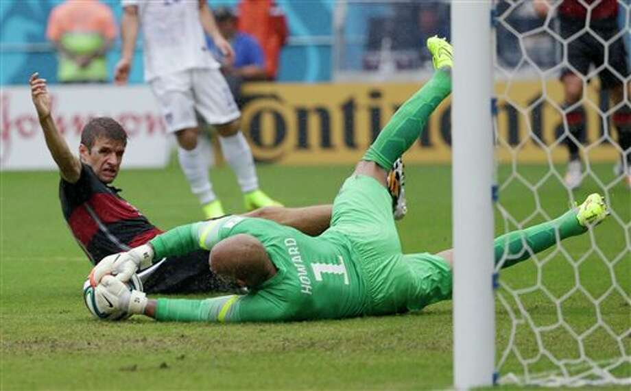 United States' goalkeeper Tim Howard dives to make a save on Germany's Thomas Mueller during the group G World Cup soccer match between the USA and Germany at the Arena Pernambuco in  Recife, Brazil, Thursday, June 26, 2014. (AP Photo/Ricardo Mazalan)