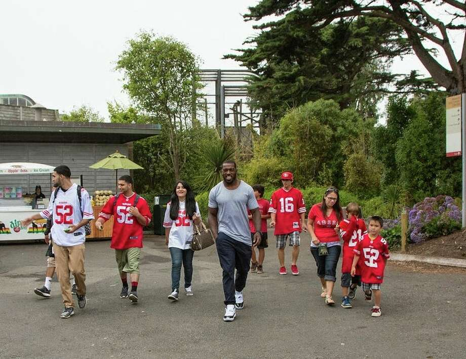 "San Francisco 49ers linebacker Patrick Willis walks with the winners of the Day at the Zoo contest at San Francisco Zoo on Wednesday, June 25, 2014. Photo: Marianne Hale, San Francisco Zoo / ""Pacifica Arts, Inc."""
