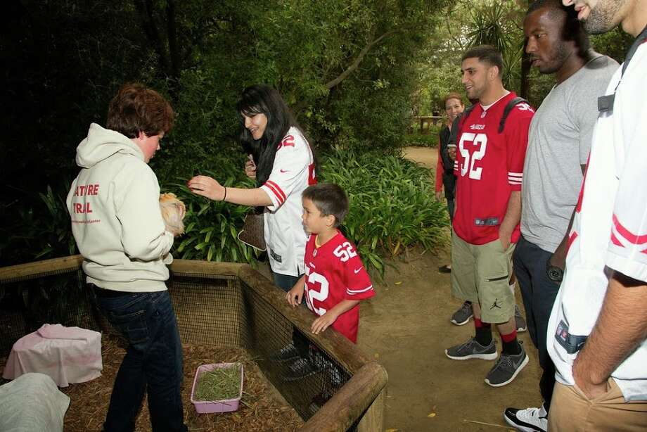 "San Francisco 49ers linebacker Patrick Willis and the winners of the Day at the Zoo contest meet a guinea pig at San Francisco Zoo on Wednesday, June 25, 2014. Photo: Marianne Hale, San Francisco Zoo / ""Pacifica Arts, Inc."""