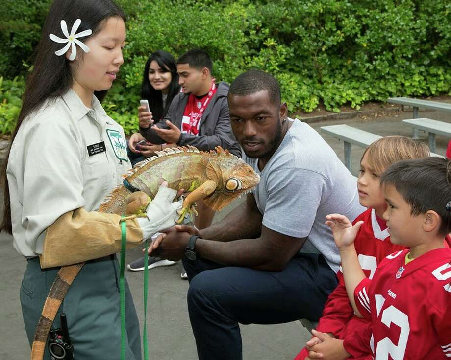 "San Francisco 49ers linebacker Patrick Willis and the winners of the Day at the Zoo contest meet an iguana at San Francisco Zoo on Wednesday, June 25, 2014. Photo: Marianne Hale, San Francisco Zoo / ""Pacifica Arts, Inc."""