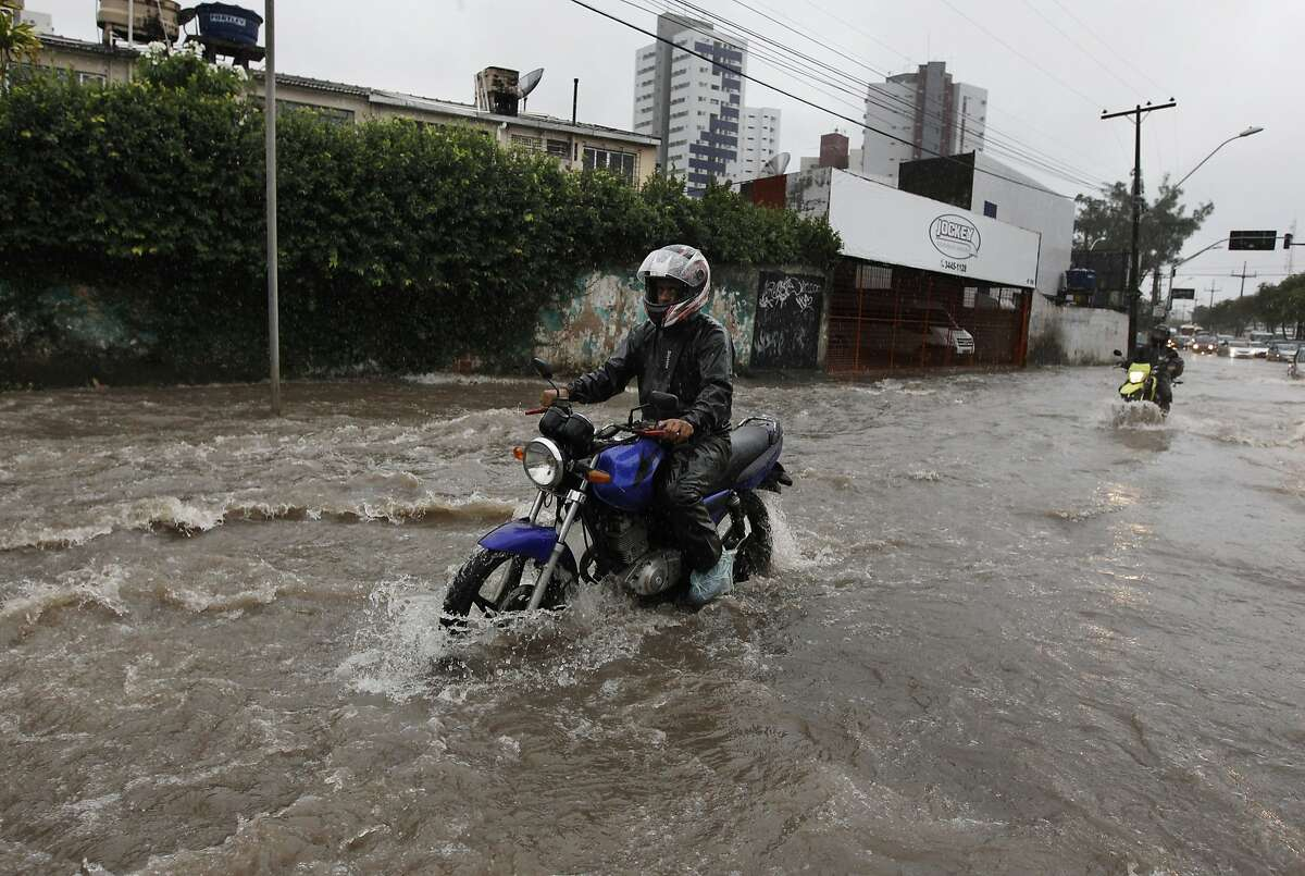 Motorcyclists make their way down a flooded street after heavy rain storms in Recife, Brazil, Thursday, June 26, 2014.