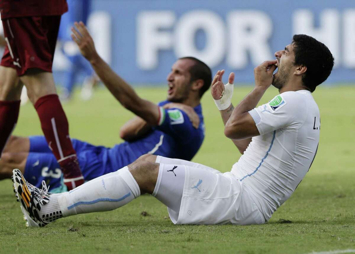 FILE - In this June 24, 2014 file photo, Uruguay's Luis Suarez holds his teeth after biting Italy's Giorgio Chiellini's shoulder during the group D World Cup soccer match between Italy and Uruguay at the Arena das Dunas in Natal, Brazil. On Thursday, June 26, 2014, FIFA banned Suarez for 9 games and 4 months for biting his opponent at the World Cup.