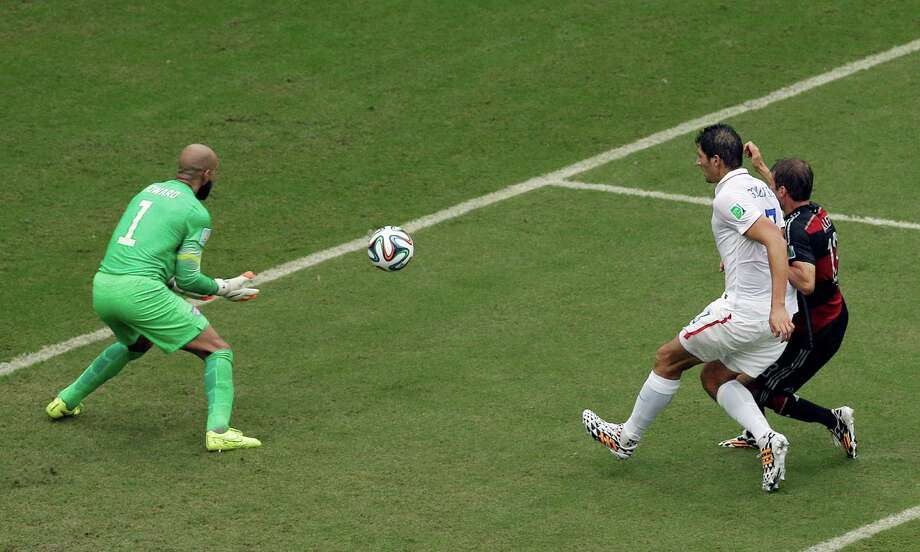 Germany's Thomas Mueller, right, takes a shot which is stopped by United States' goalkeeper Tim Howard as United States' Omar Gonzalez moves into the playt during the group G World Cup soccer match between the USA and Germany at the Arena Pernambuco in Recife, Brazil, Thursday, June 26, 2014. (AP Photo/Hassan Ammar) Photo: Hassan Ammar, Associated Press / AP2014