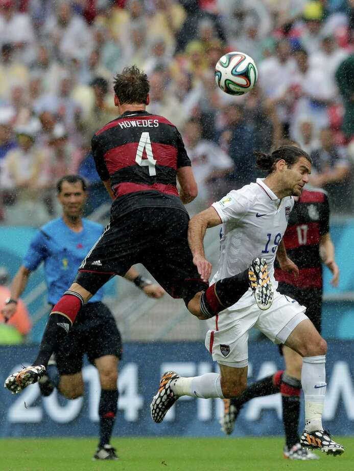 Germany's Benedikt Hoewedes, left, and United States' Graham Zusi go for a header during the group G World Cup soccer match between the USA and Germany at the Arena Pernambuco in Recife, Brazil, Thursday, June 26, 2014. (AP Photo/Matthias Schrader) Photo: Matthias Schrader, Associated Press / AP